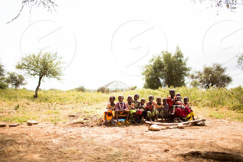 1 adult female sitting with children near grass and trees field during daytime photo