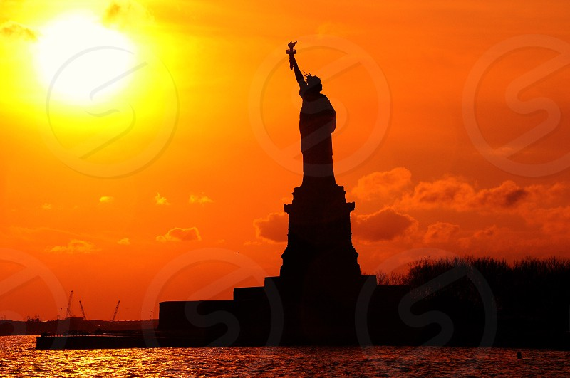 silhouette of statue of liberty below orange sky during twilight photo