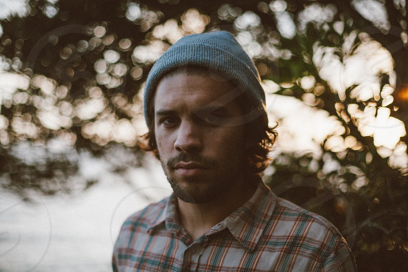 man with grey knit hat and plaid shirt photo