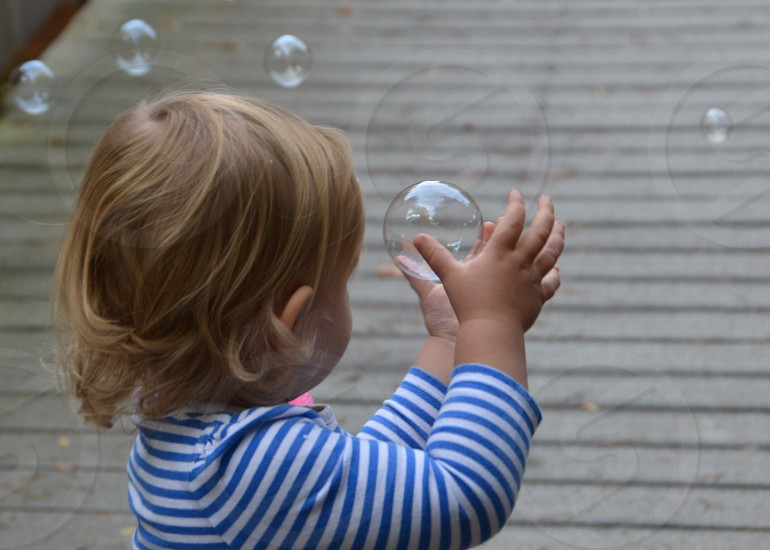 Toddler catching bubble photo