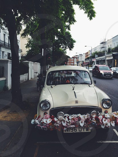 white classic car parked beside road photo