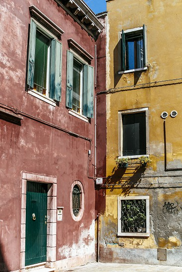 venice buildings facades door windows decaying aged red green patina deteriorating italy house wall yellow photo