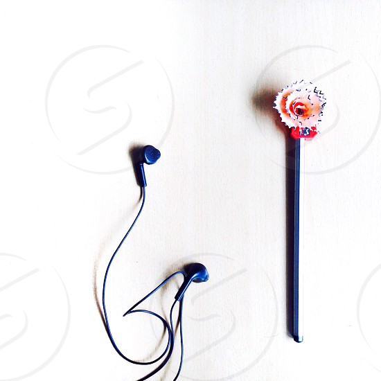 blue corded headphones beside gray stick on top of gray surface photo