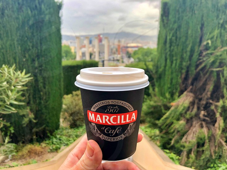 Walk around Barcelona.  Disposable paper coffee cup in the hand. Personal perspective.  photo