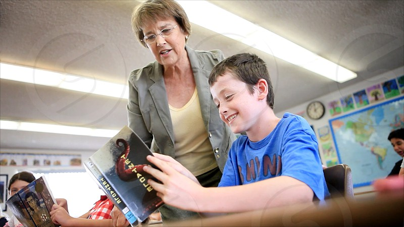 A female teacher discusses a reading book to a junior high boy while looking over his shoulder at his desk. photo