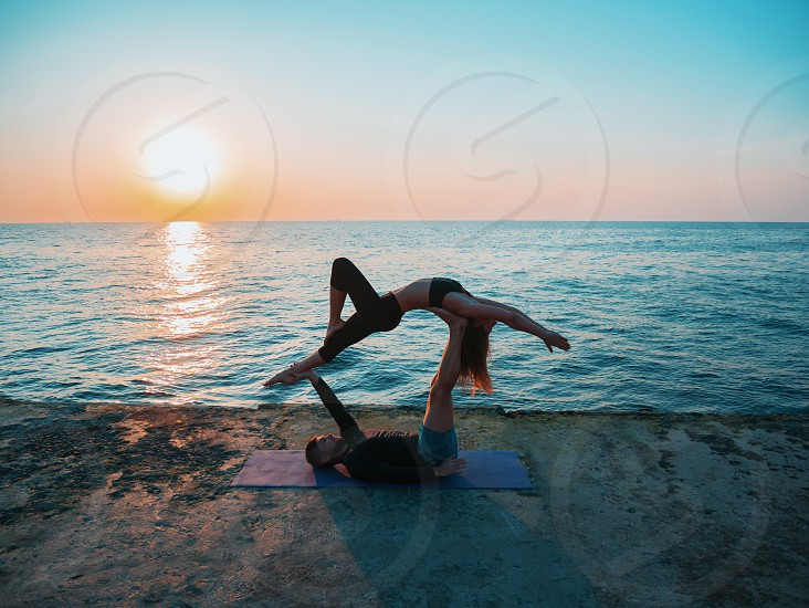 Young beautiful couple practicing acro yoga on the sea beach near water. Man and woman doing everyday practice outdoor on nature background. Healthy lifestyle concept. photo