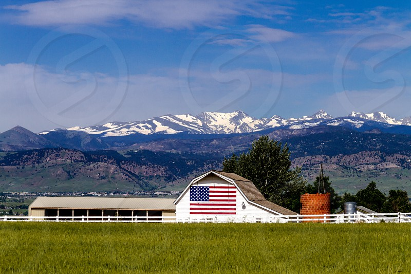 White barn with American flag painted on the side in front of the Rocky Mountains photo