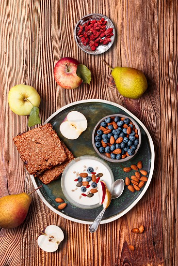 Breakfast on table. Yogurt with added blueberries and roasted almonds. Muesli cookie apples and pears on wooden table. Light and healthy meal. Good quality balanced diet. Flat top-down composition photo