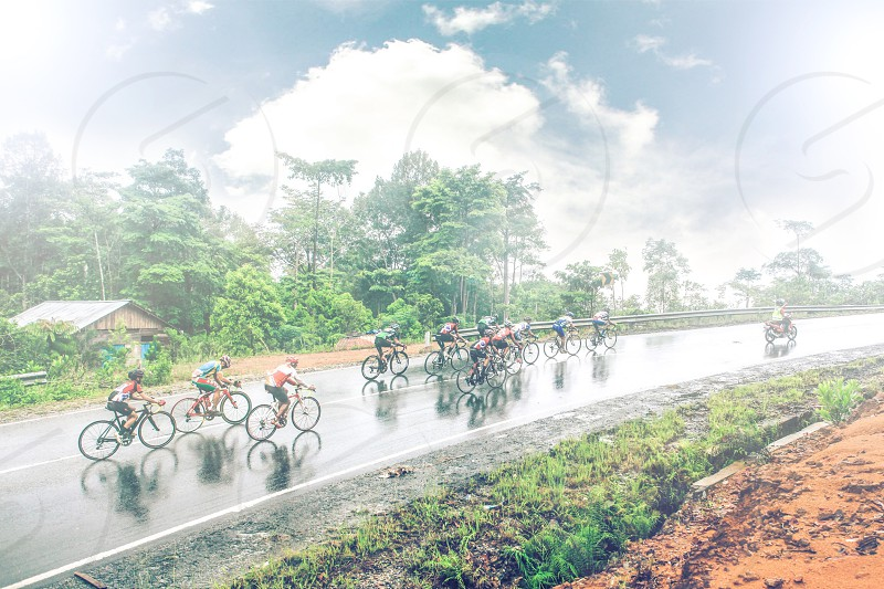 photo of group of cyclist on wet road surrounded by green trees and grass under white clouds and blue sky during daytime photo