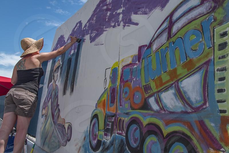 Woman painting construction site mural Denver Colorado photo