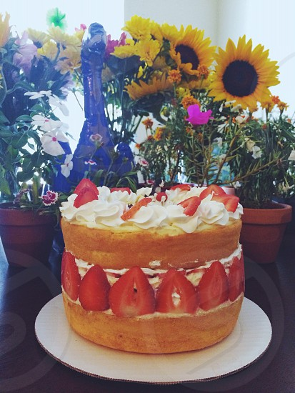 Birthday cake: strawberry shortcake with whipped cream frosting in front of wildflowers and potted plants for a celebration.  photo
