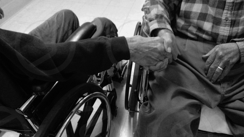 2 person in wheelchairs holding hands photo