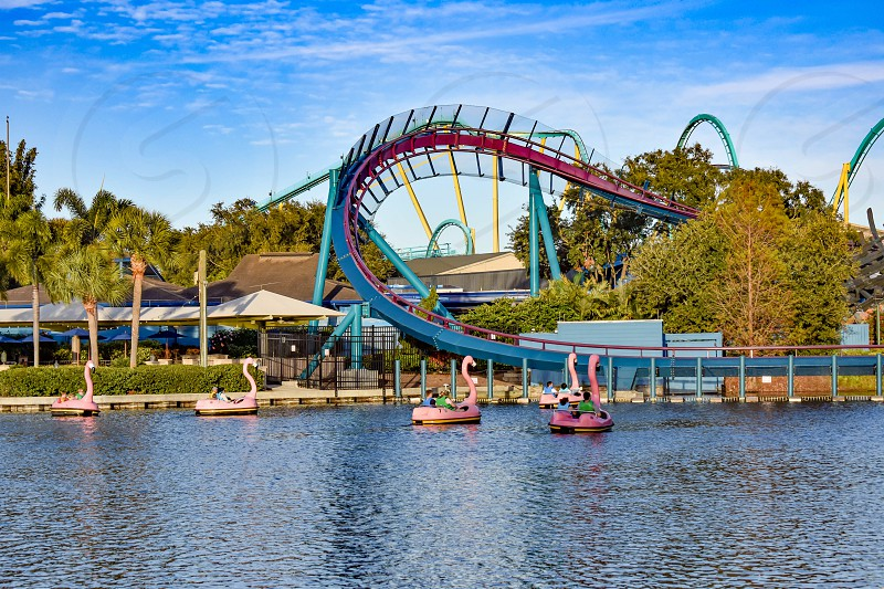 Orlando Florida. December 19 2018. at Seaworld Panoramic view of roller coaster and flamingo boat ride on blue lake in International Drive area photo