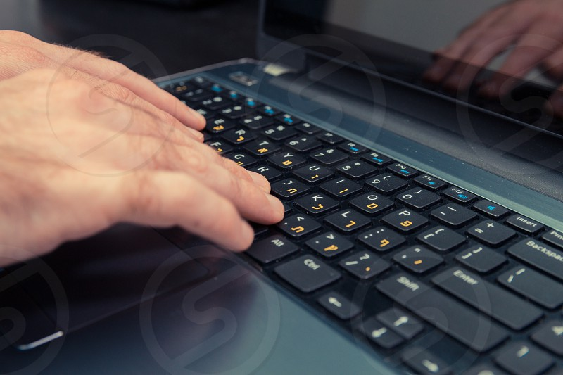 Man typing on a keyboard with letters in Hebrew and English - Laptop keyboard photo