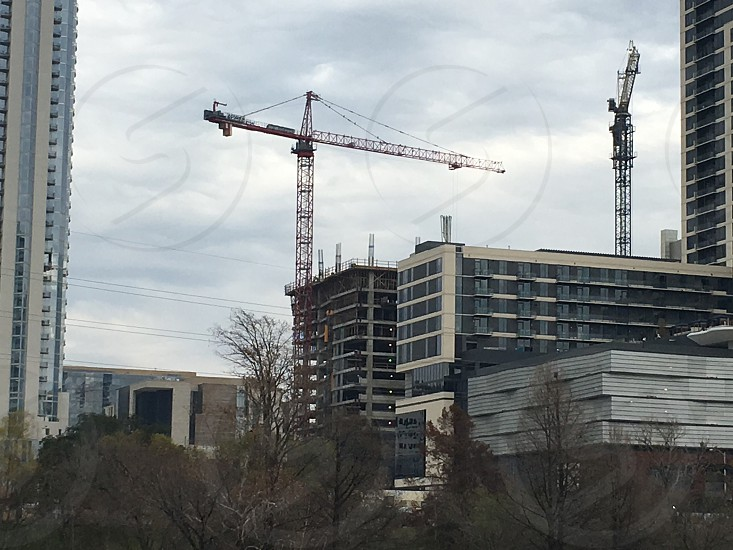 black crane near white and gray building under white cloudy sky photo