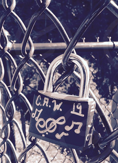 crw 19 and music notes printed black and grey padlock in chain linked fence photo
