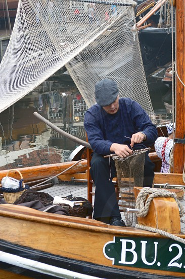 Dutch fisherman repairing and making fishnets photo