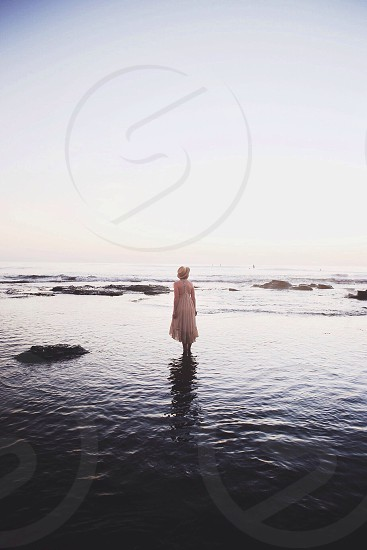 woman wearing brown backless dress in water during sunset photo