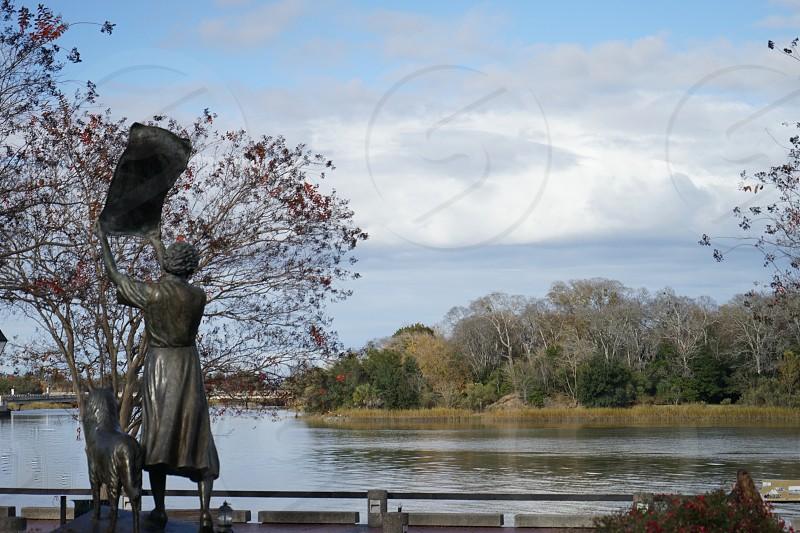 Waving girl statue in Savannah Georgia. river vegetation sculpture dog towel clouds photo