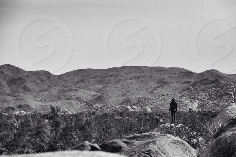 grayscale mountain range view with human standing at the stone formation photograph  photo