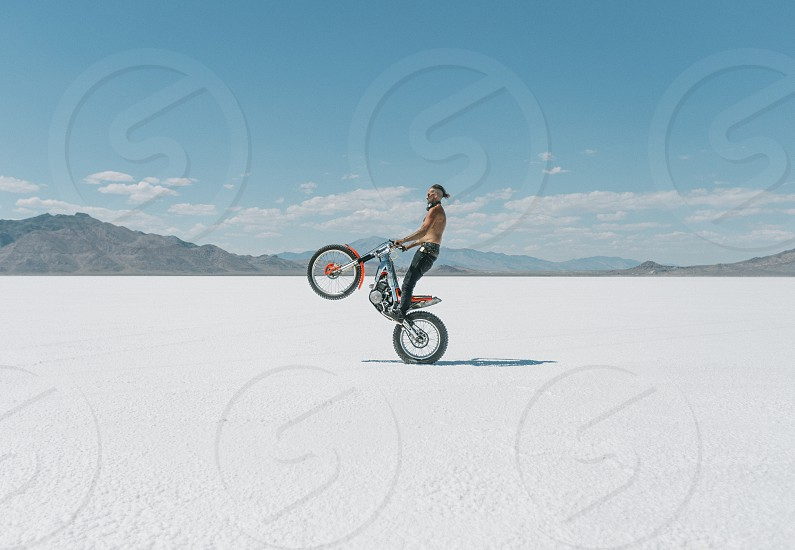 A biker on the Bonneville Salt flats in Utah perfecting his wheelie for an upcoming race.  photo