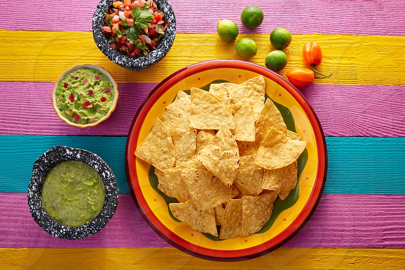 Nachos tortilla chips with mexican sauces on colorful table photo