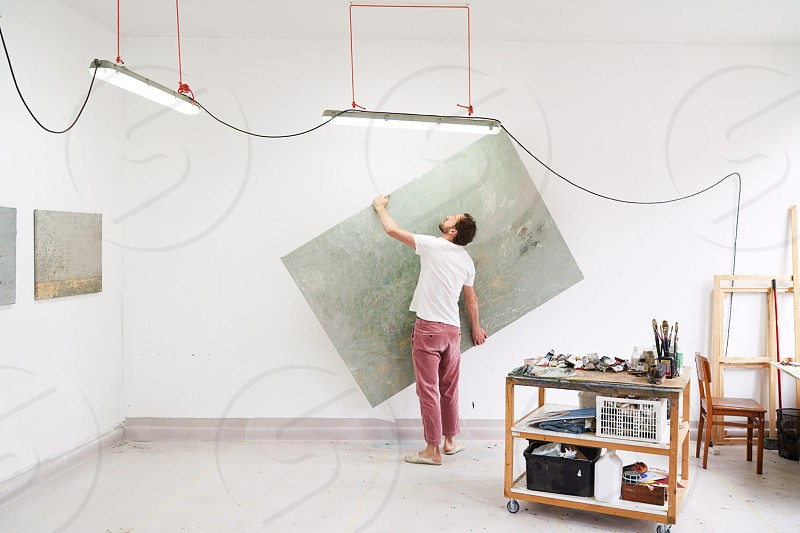 An artist lifts up a painting in his studio. photo