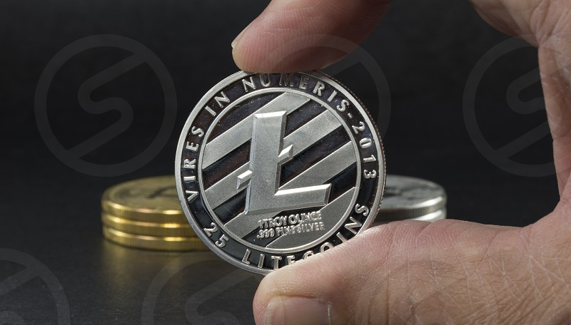 hand showing litecoin with black background with a single litecoin facing the camera in sharp focus with shading on the icon letter B on the face of the bit coin photo