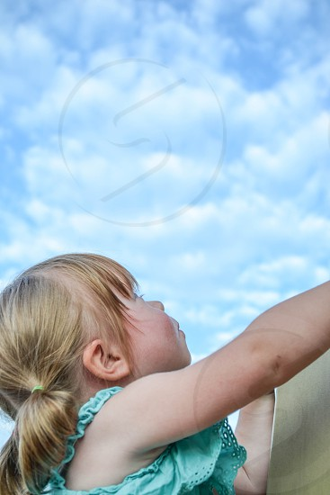 little girl climbing up looking into the blue and white clouds sky photo