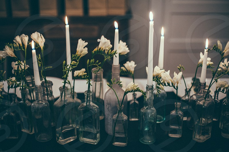 lighted candle on table with flower in bottle photo