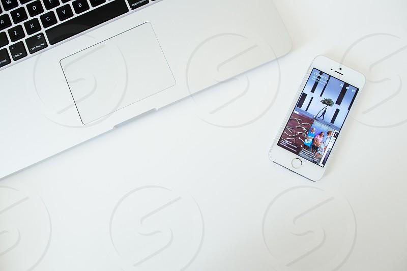 white iphone 5 beside white laptop  photo