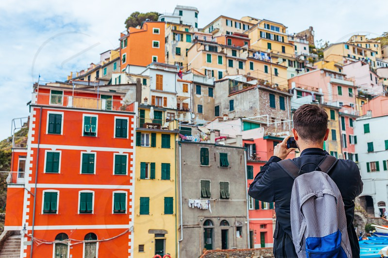 Young man traveling through Europe and taking picture Cinque Terre Italy photo