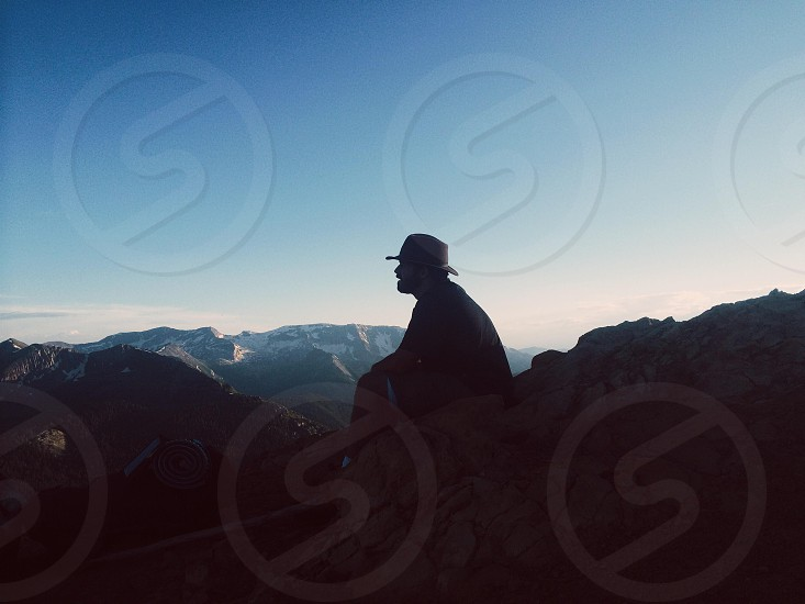 man in black hat and black t shirt sitting on rock photo