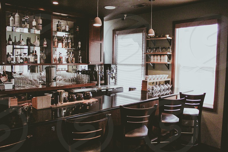 empty bar stool near bar counter table with wines on shelf during daytime photo