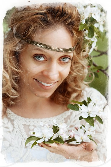 Girl in apple blossoms. Pretty face beautiful yes hairs smile. Film. photo