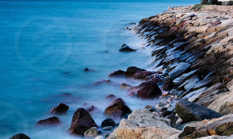 blue water by rocky beach shore photo
