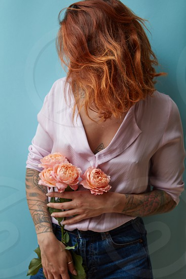 Sexy girl with pink roses media on a blue background. Concept of Valentine's Day Mother's Day photo