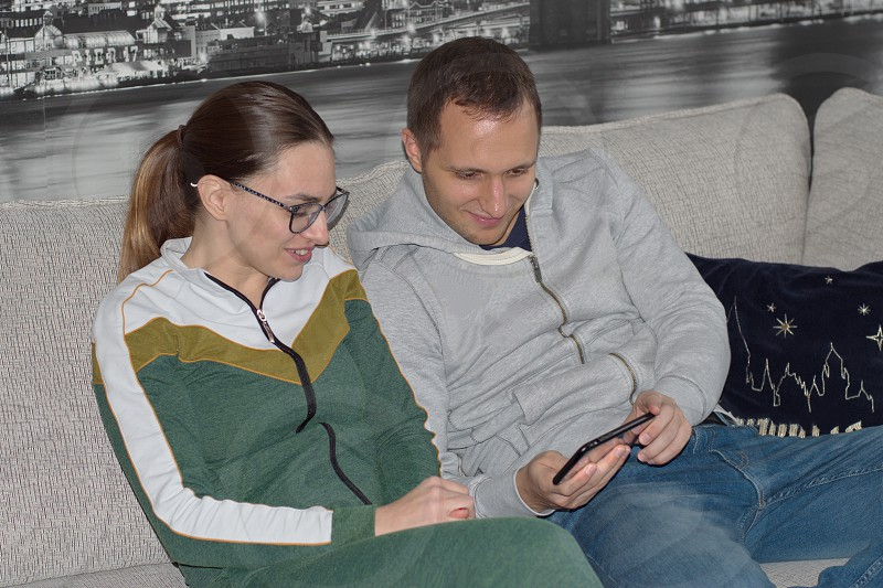 Young couple sitting on the sofa using mobile phone photo