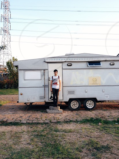 man wearing white crewneck t shirt and black pants standing near door of silver trailer photo