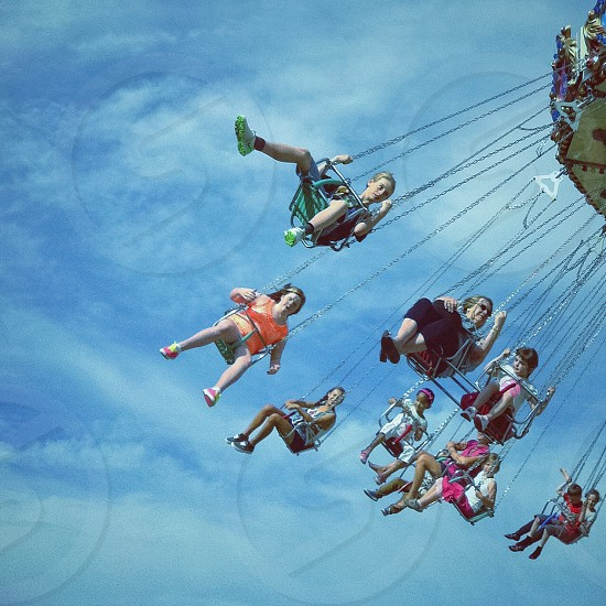 photo of a amusement park swing ride down the shore during daytime photo