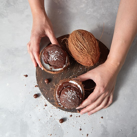 Homemade chocolate ice cream in a coconut shell with whole coconut holding womans hands on a gray concrete background with place for text. Summer dessert. photo