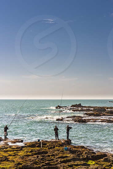 Cadiz Spain - Dec 2018: Men fishing off the rocks of Paseo Fernando Quinones photo