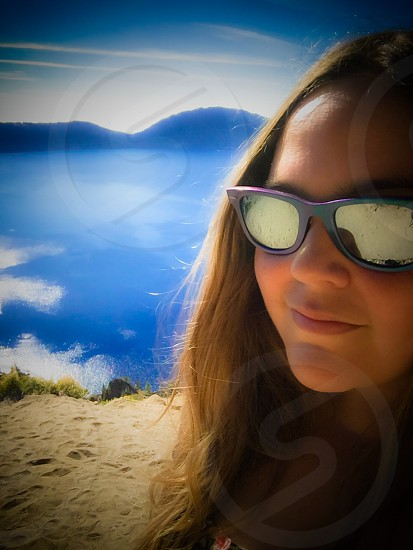 Outdoor day colour vertical portrait Crater Lake caldera lake Chemult Klamath County Klamath Oregon OR West western United States US USA America North America road trip travel tourism tourist wanderlust blue summer trees evergreen nature natural lake sheen shine glimmer gleam square roots leaves sand wood grooves Wizard Island view vista filter shore photo