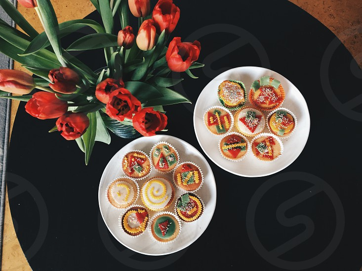 assorted-color cupcakes on white ceramic plates photo