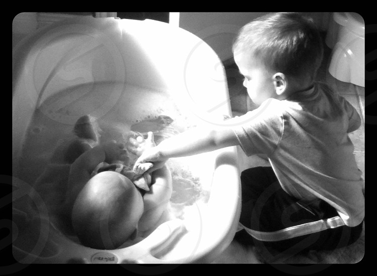 black and white photo of a boy giving an infant a bath photo