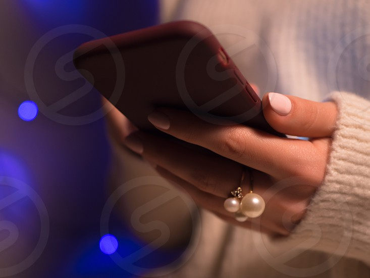 Close-up image of female hands using smartphone at night on city shopping street searching or social networks concept hipster typing sms message to his friends photo