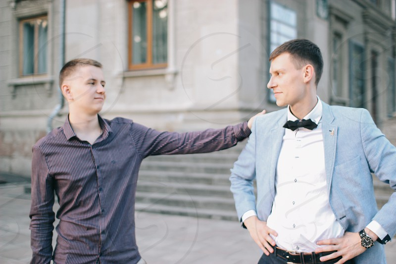 Man supports his friend keeping hand on his shoulder photo