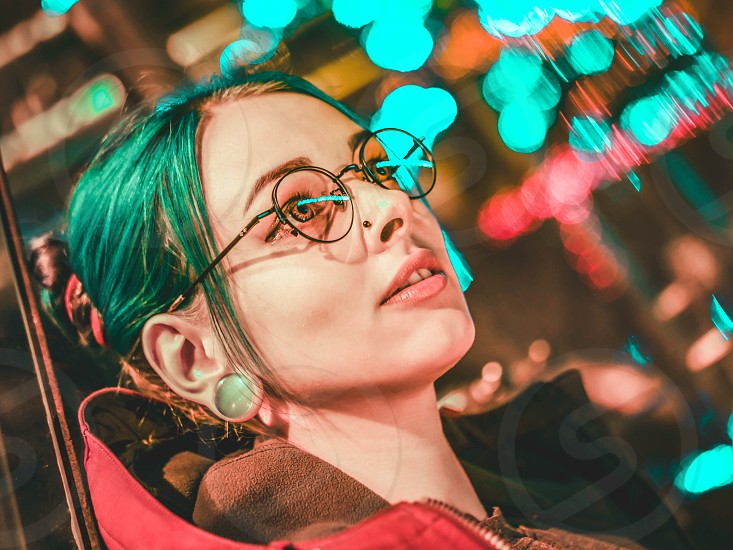 Millennial pretty girl with unusual hairstyle near glowing red neon of city at night. Dyed blue hair in braids. Mysterious hipster teenager in glasses. Reflection of light. photo