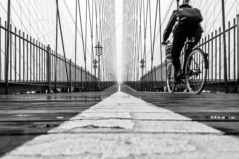 person riding bicycle across brown bridge in grayscale photo