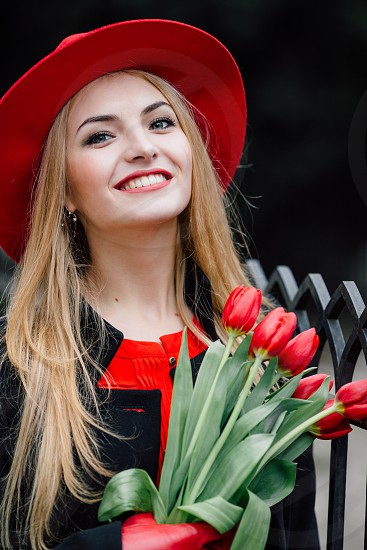 smiling woman in red and black shirt holding red tulips flowers during daytime photo